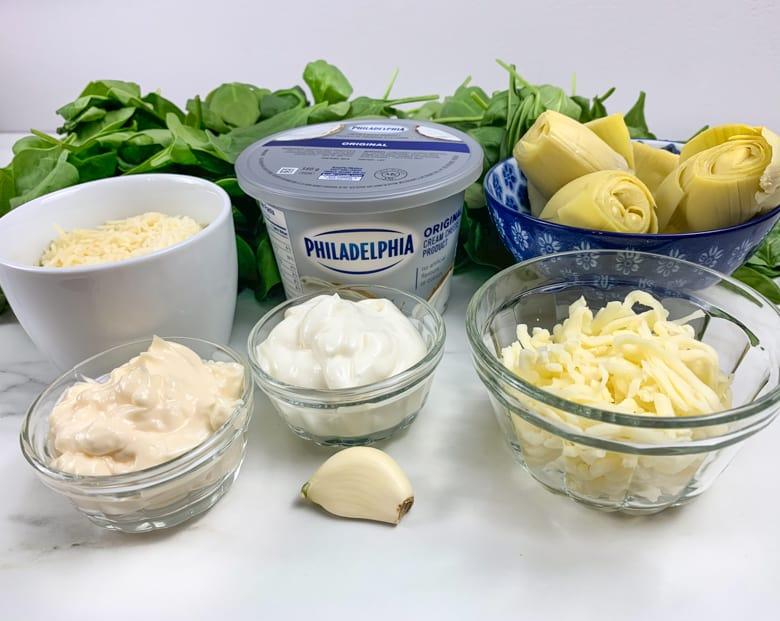 Spinach Dip Ingredients: grated Parmesan, shredded mozzarella, cream cheese, sour cream, artichoke hearts, fresh spinach, and a garlic clove,