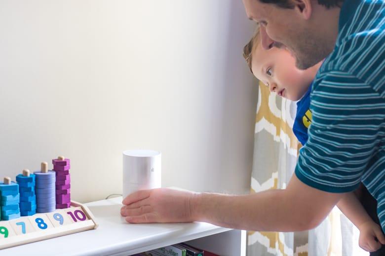 Man holding toddler placing ibi device on bookshelf