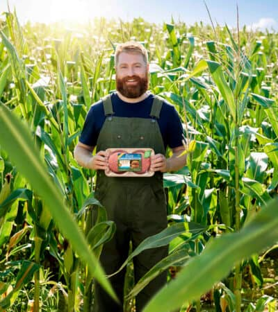 Man in cornfield holding Pure Farmland product