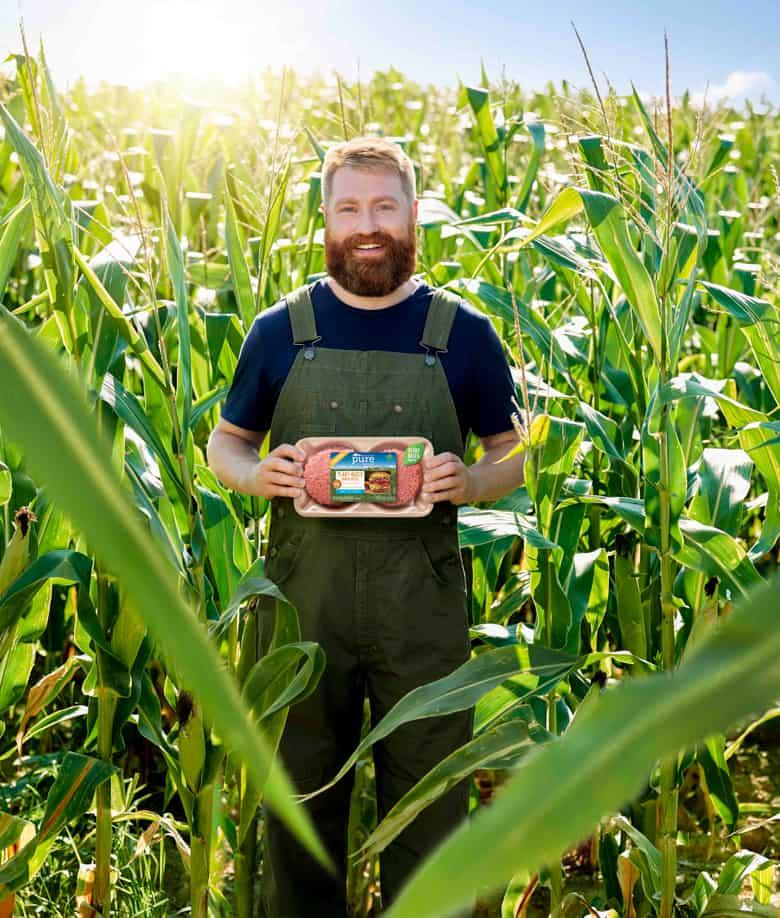 Man in cornfield holding Pure Farmland product
