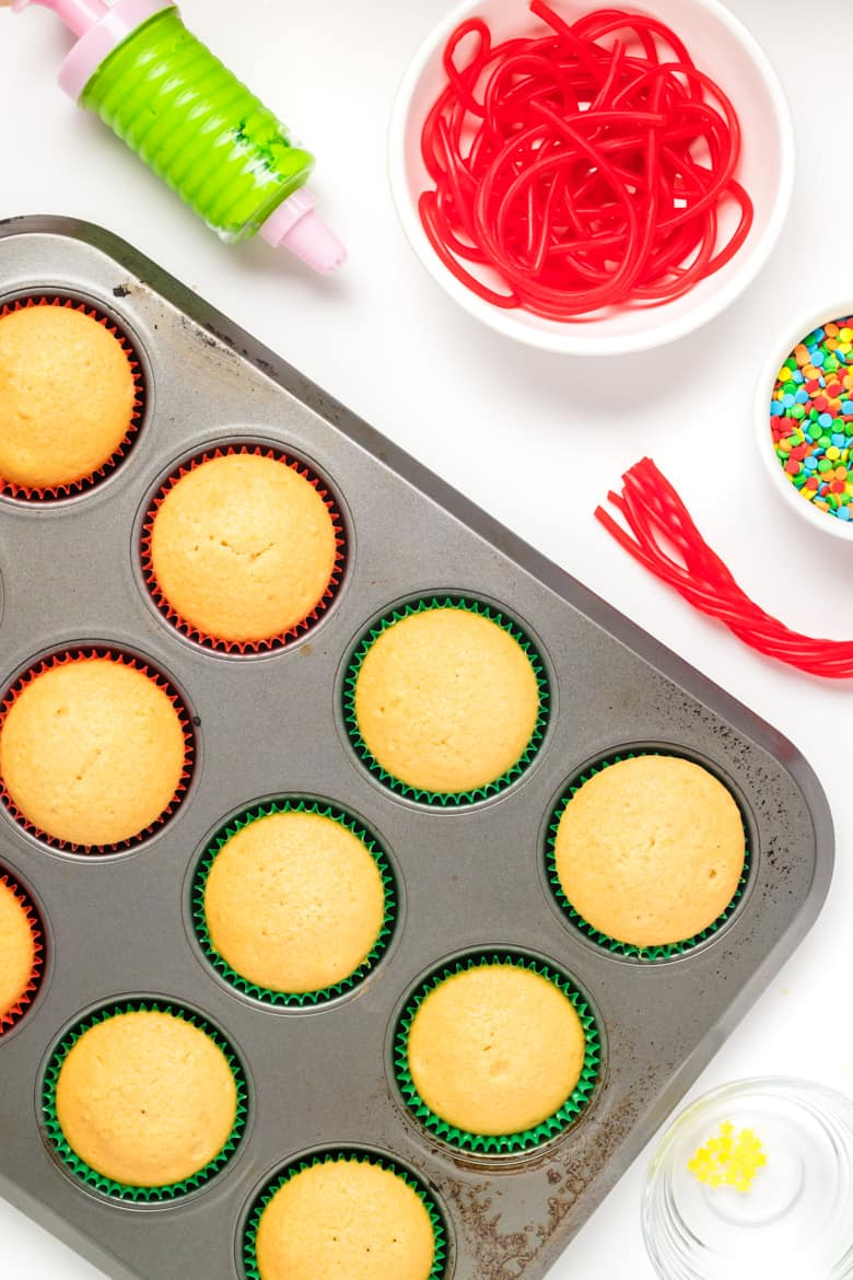 Vanilla cupakes in cupcake pan next to green frosting in piper, red string candy, and sprinkles