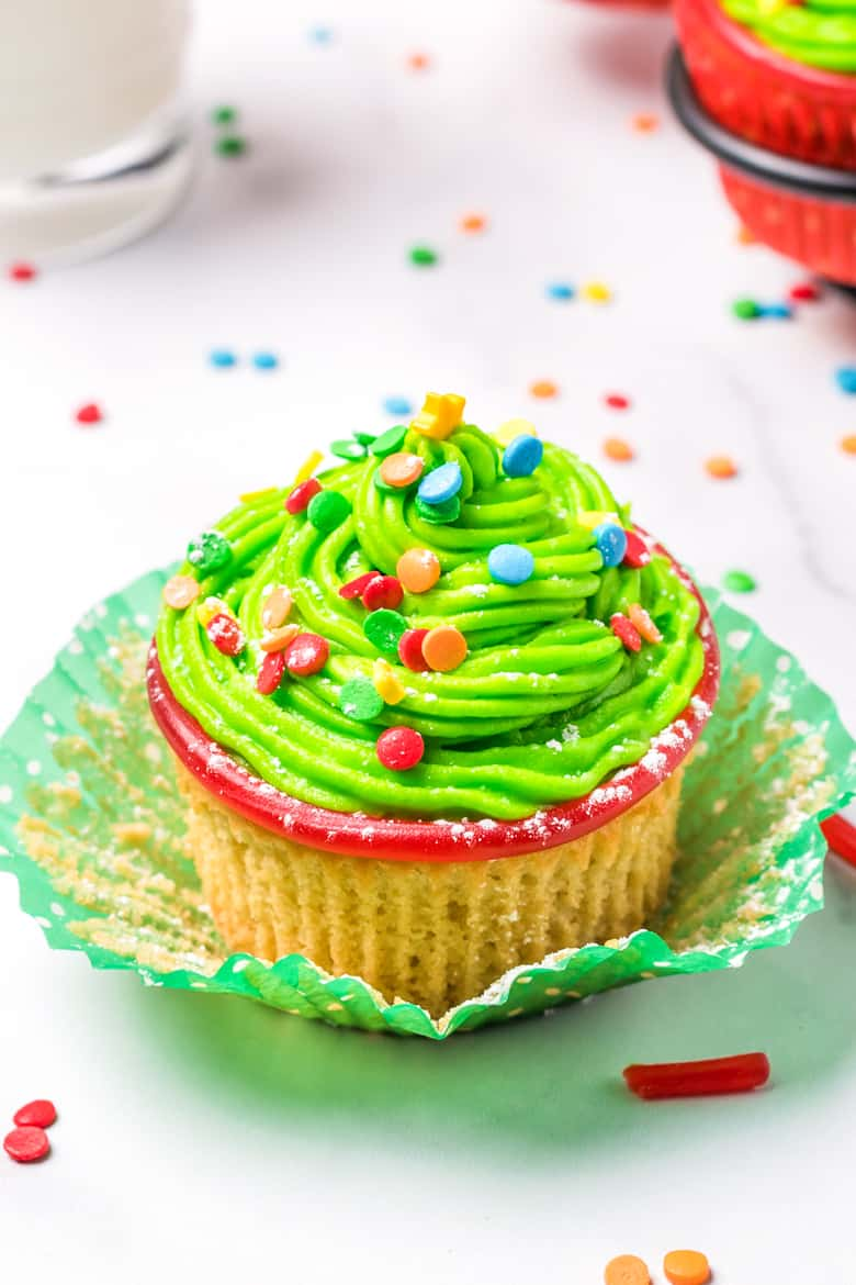 Cupcake with green frosting and rainbow sprinkles