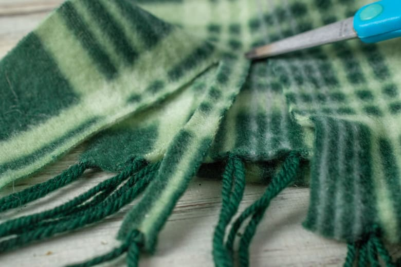 Green plaid scarf being cut into strips with scissors