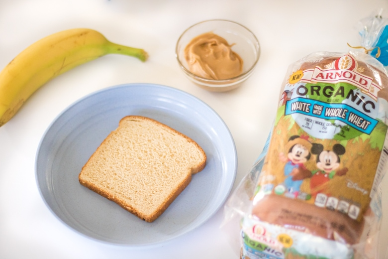 banana, slice of bread on blue plate, small bowl of peanut butter, loaf of Arnold Organic for Kids Bread