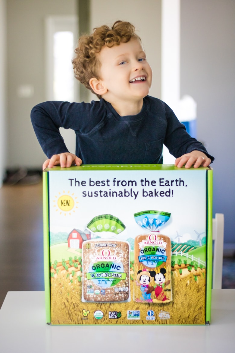 Young boy standing over box that reads: The best from the Earth sustainably baked and showing Arnold Organic Bread