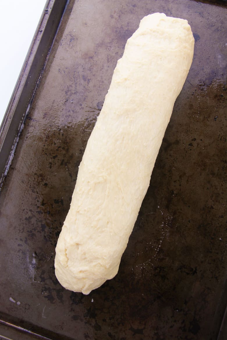 Bread dough formed into a long log on a baking sheet