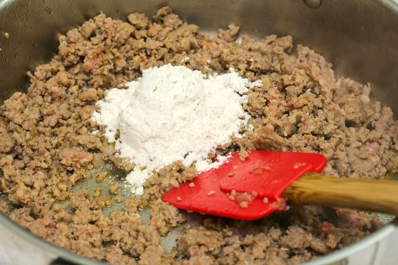 Large skillet of browned sausage topped with flour