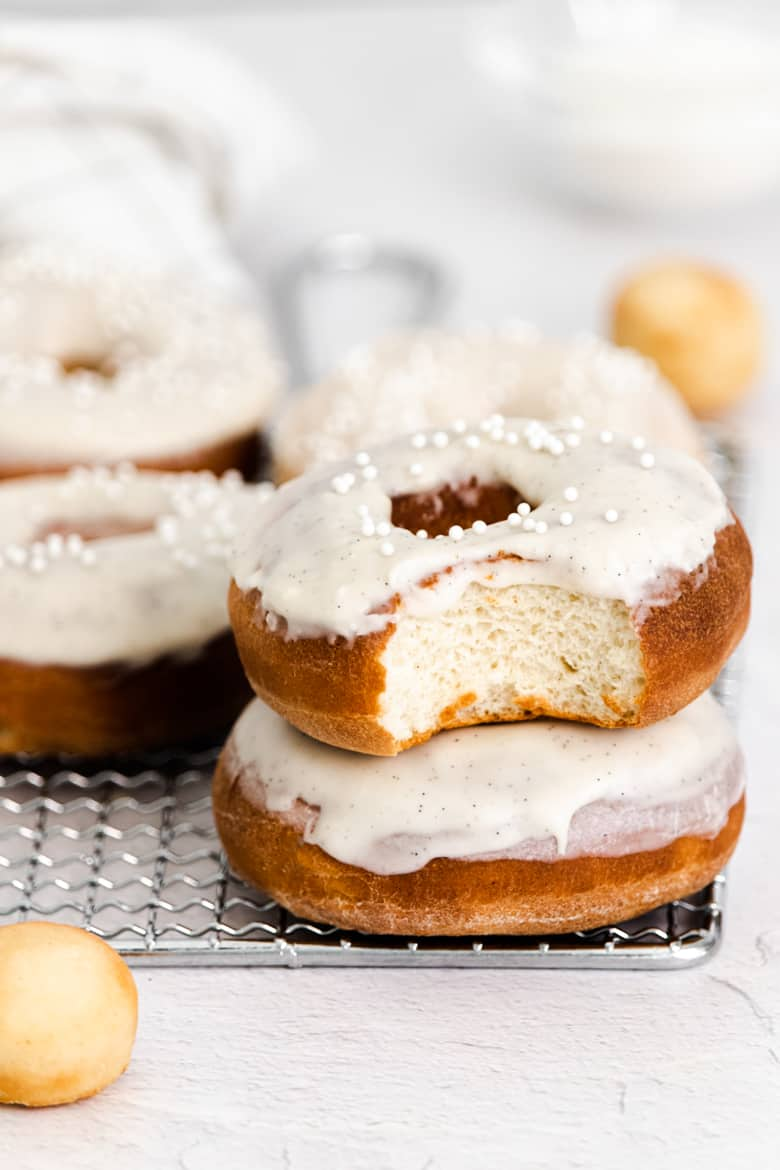 several homemade air fryer donuts with vanilla icing, one with bite taken out of it to show cake-like inside