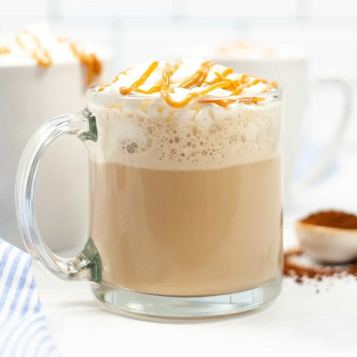 Caramel Macchiato topped with whipped cream and a drizzle of caramel in glass mug