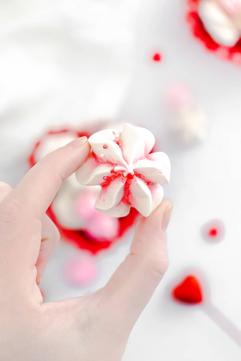 hand holding a valentine's day meringue cookie