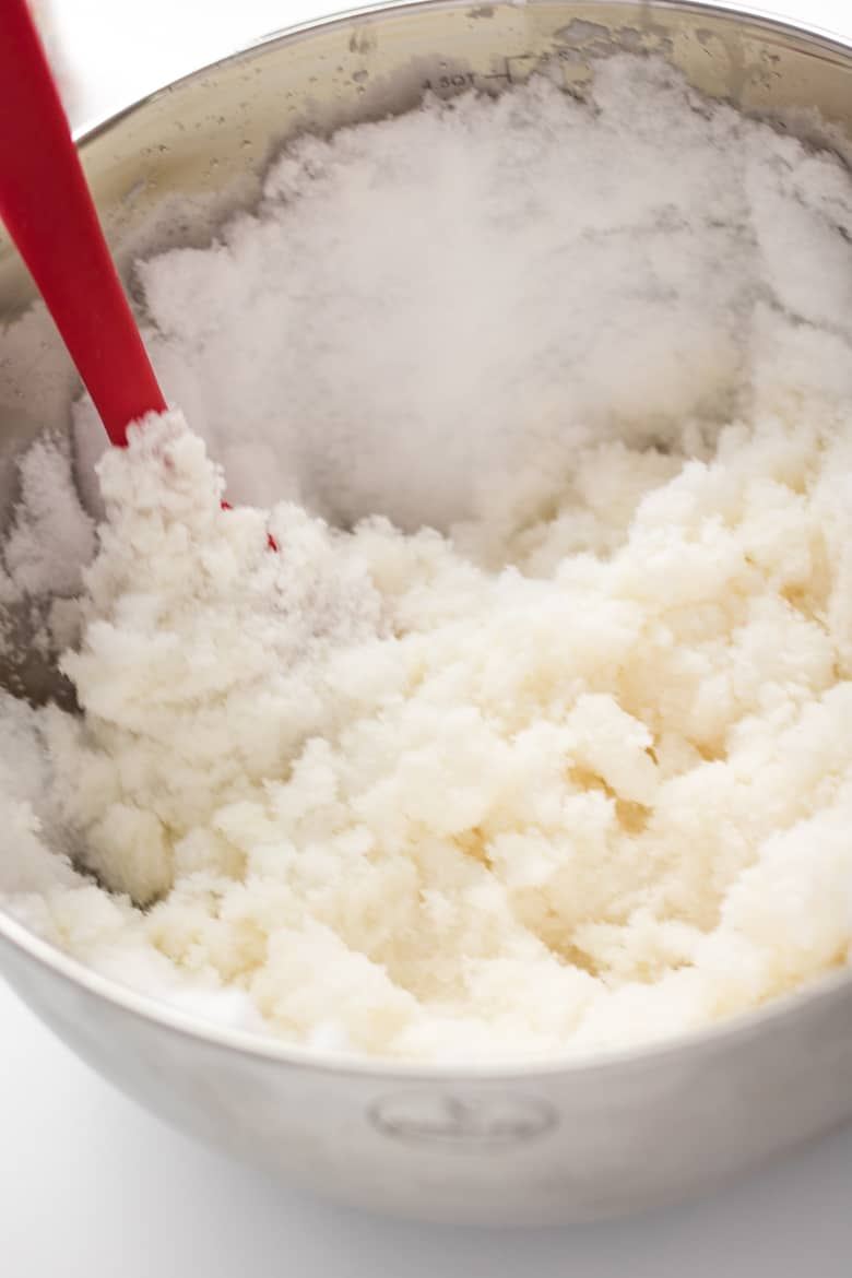 homemade ice cream in a large silver bowl with red spatula