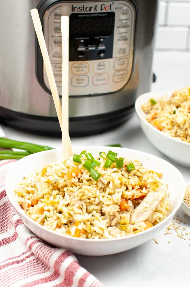 Chicken fried rice topped with green onions in a white bowl. Chopsticks are sticking up out of the bowl and an Instant Pot is in the background.