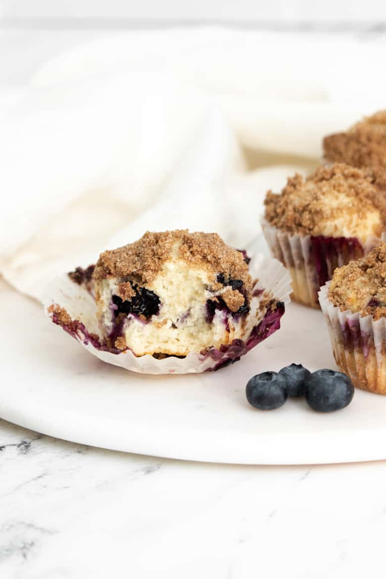 Lemon and Blueberry Muffin with wrapper off and bite taken out of it to show soft and fluffy inside
