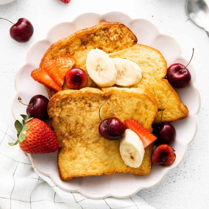 Three pieces of brioche french toast plated with banana slices and fresh berries