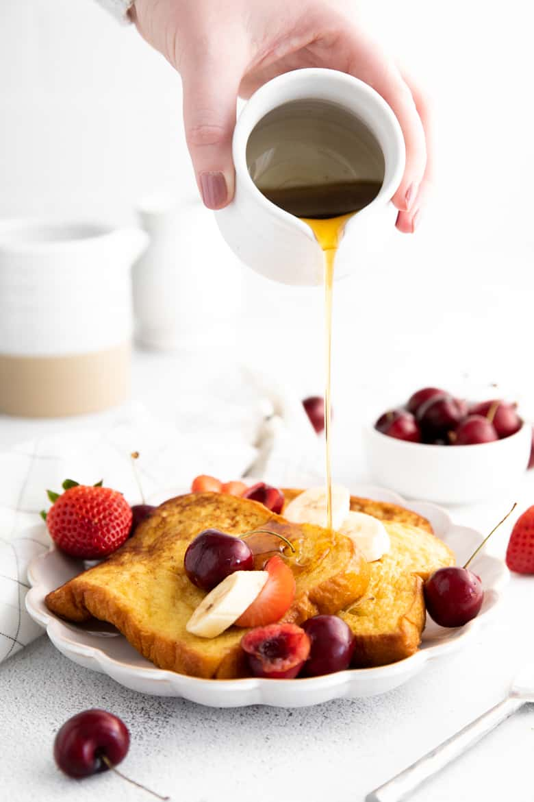 Hand pouring pitcher of maple syrup over french toast with topped with fresh fruit. Bowl of cherries in background