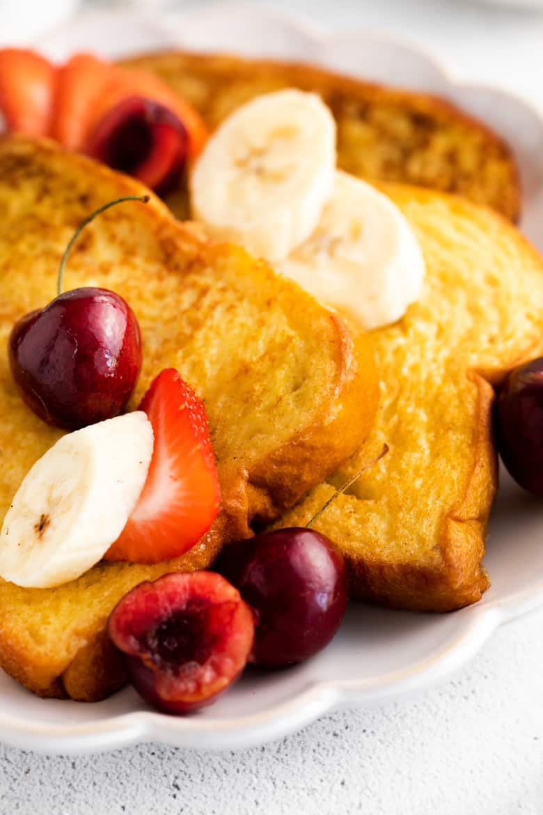 Thick sliced fluffy brioche french toast topped with slices of banana and strawberries, and fresh cherries.