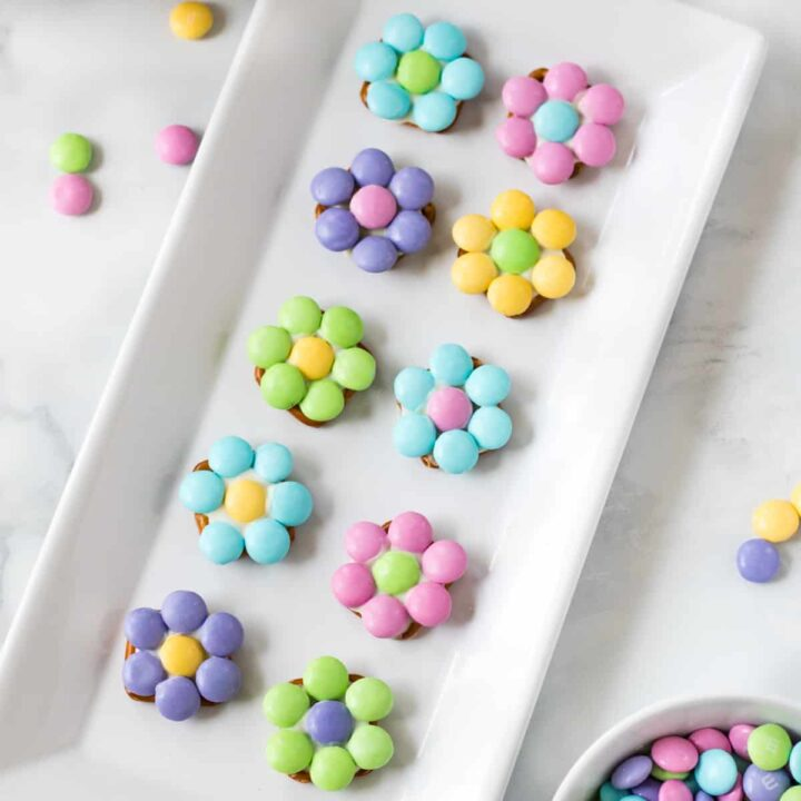 10 pastel-colored flowers made from M&Ms and pretzels displayed on a white serving plate with additional M&Ms sprinkled around the tabletop