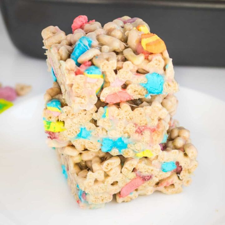 Three lucky charms marshmallow cereal bars cut into squares and stacked on top of one another on a white plate