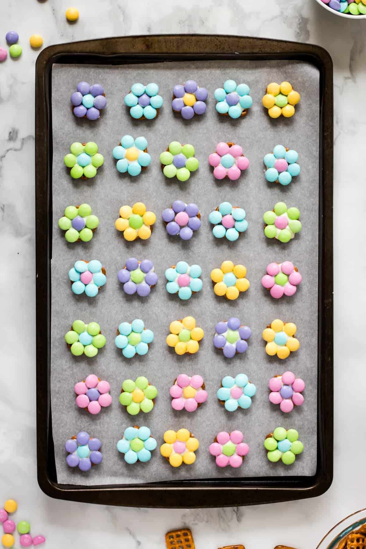 M&M Pretzel flower bites arranged in even rows on lined baking sheet