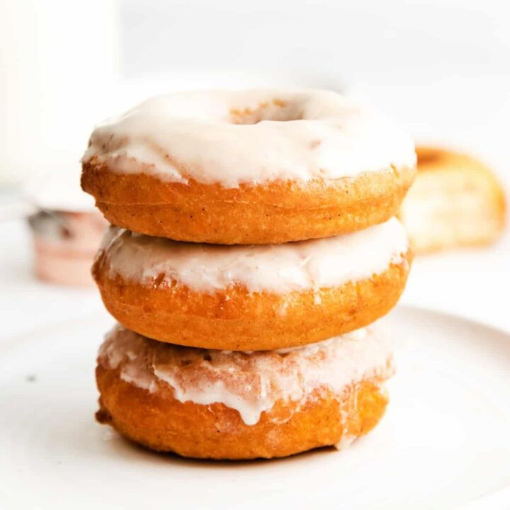 Three glazed doughnuts stacked on top of one another, set atop a white plate