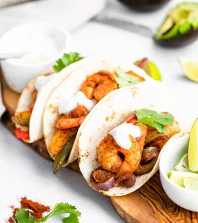 Sheet Pan Shrimp Fajitas served in flour tortillas topped with fresh cilantro and sour cream