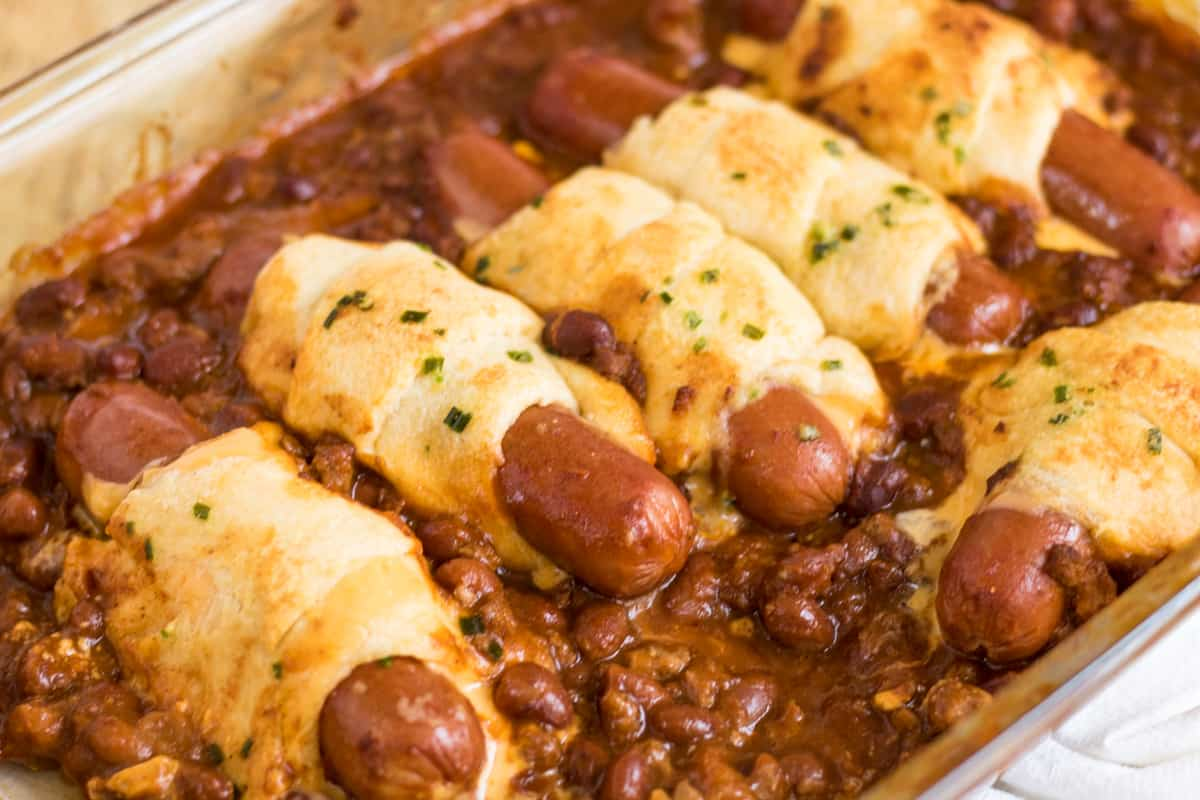 Chili cheese dog casserole made with hot dogs wrapped in cheese and crescent rolls and surrounded by chili