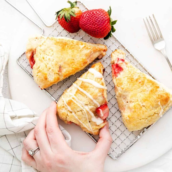 Woman's hand reaching to take a homemade strawberry scone