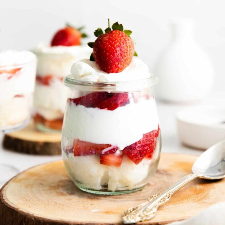 strawberry, angel food cake, and whipped cream trifle in small glass jar