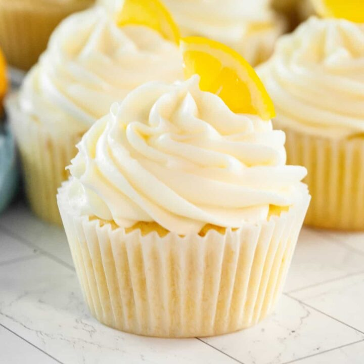 Lemon cupcakes topped with cream cheese frosting and garnished with a slice of lemon