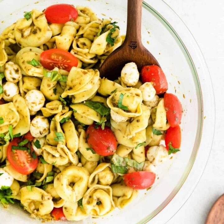 Wooden serving spoon in a bowl of tortellini pasta salad with pesto dressing