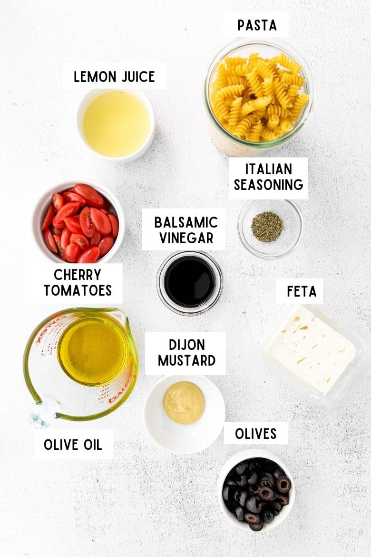 Ingredients in glass bowls: rotini pasta, olive oil, cherry tomatoes, balsamic vinegar, italian seasoning, feta, lemon juice, dijon mustard, olives
