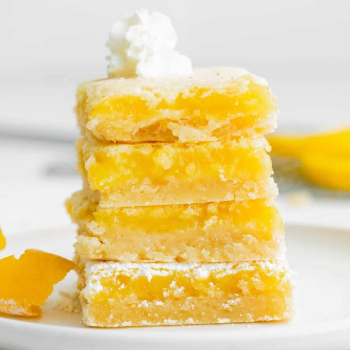 four bright yellow lemon Bars stacked on top of one another on a white plate.