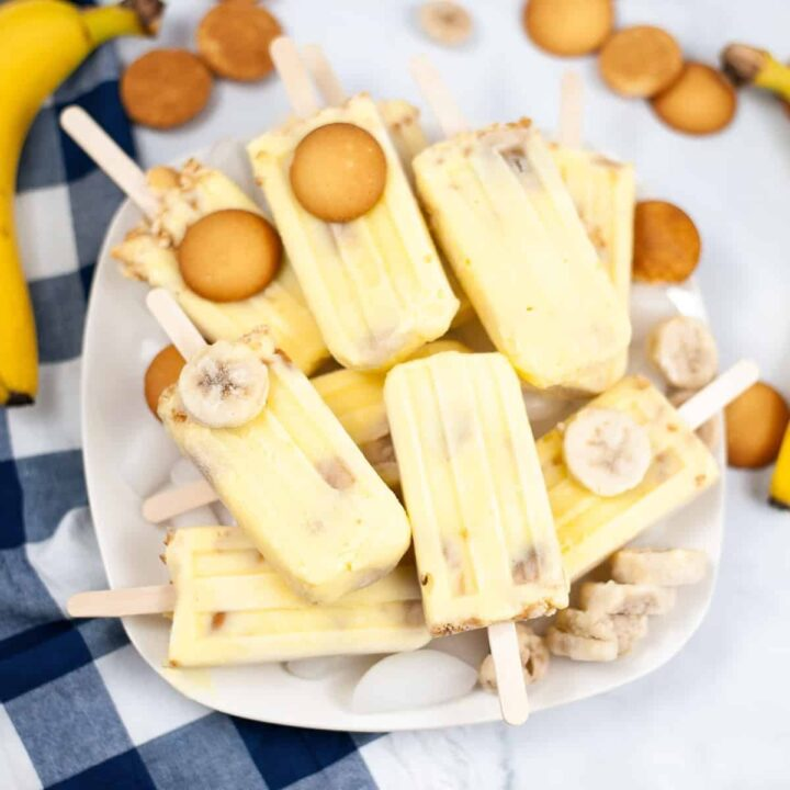 Banana popsicles piled on a platter with nilla wafers and frozen banana slices