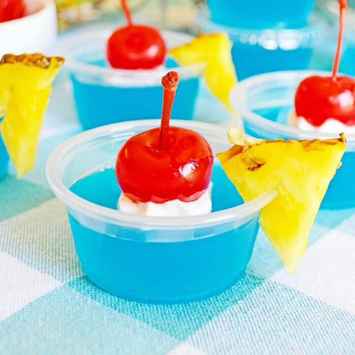 Bright blue jello shots garnished with whipped cream, cherries, and pineapple wedges