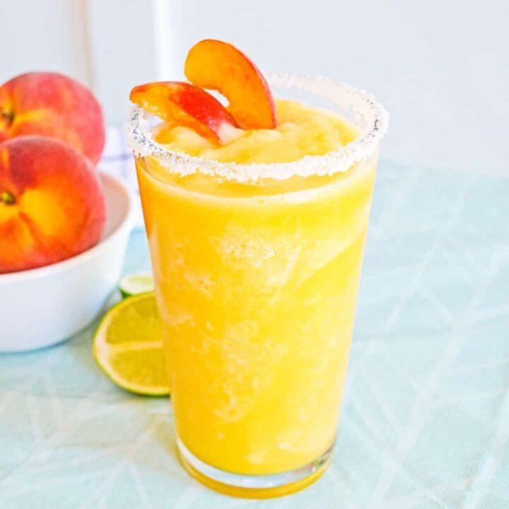 Frozen peach margarita with salt rim and garnish of fresh peach slices