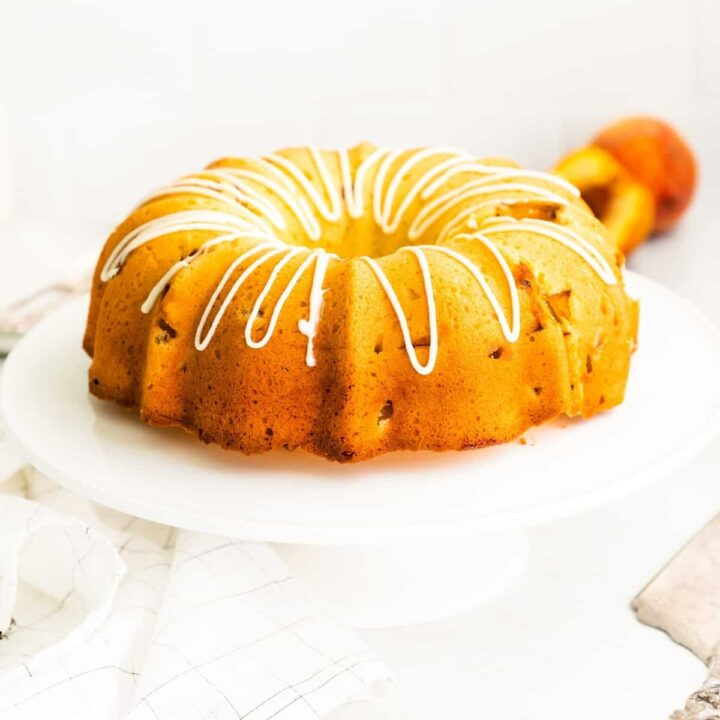 Golden bundt cake topped with drizzle of icing. Cake is on white cake stand and fresh peaches are in background.