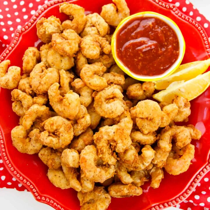 popcorn shrimp on red plate with lemon wedges and cocktail sauce