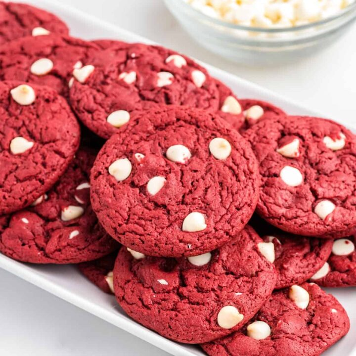 Red velvet cookies with white chocolate chips piled on white serving platter with bowl of white chocolate chips in the background