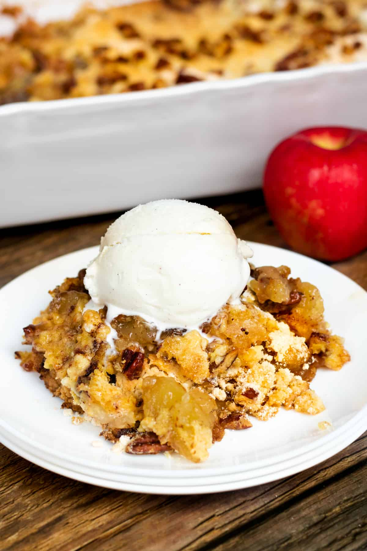 Apple dump cake served on white plate with scoop of vanilla ice cream. Baking pan with remaining cake and an apple are in background.
