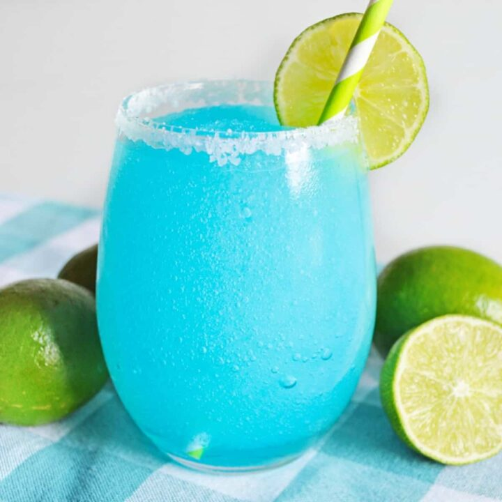 Blue lagoon margarita served in stemless glass rimmed with sugar and garnished with a slice of lime.