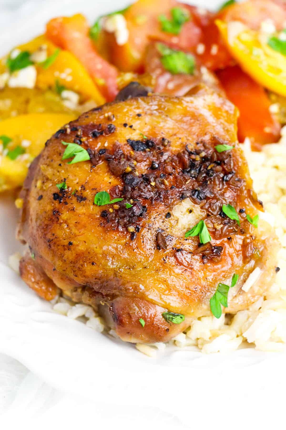 Crockpot brown sugar garlic chicken thigh served over rice with tomato salad