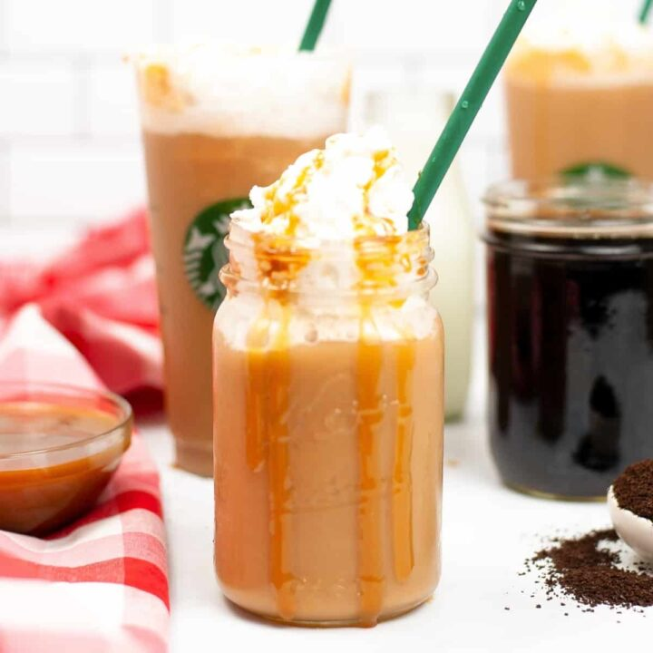 Caramel Frappuccino topped with whipped cream and caramel drizzle served in a mason jar with green straw