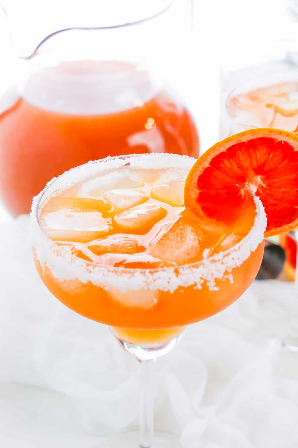 Grapefruit margarita over ice in margarita glass garnished with fresh grapefruit slice. Pitcher of grapefruit juice in background