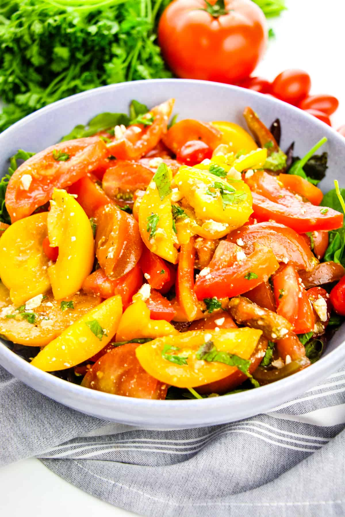 Heirloom Tomato Salad served in large grey bowl on bed of lettuce with parsley and tomatoes in background