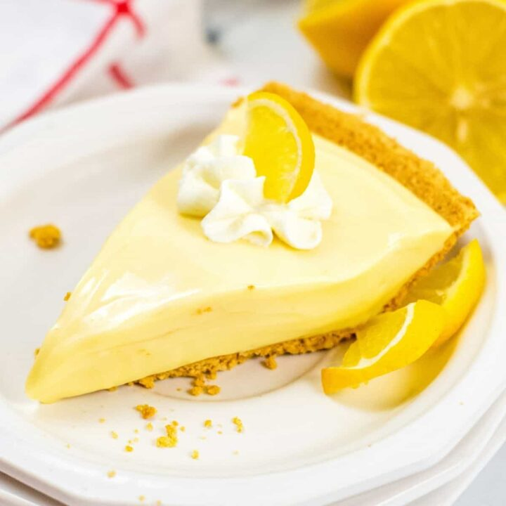 Lemon Icebox Pie slice on white plate, topped with whipped cream and lemon slice