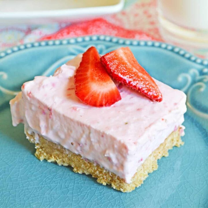 No-Bake Strawberry Cheesecake Bar with a thick graham cracker crust on blue plate topped with fresh strawberries