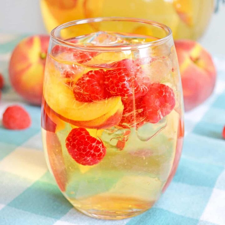 White peach sangria with fresh peaches and raspberries in a stemless wine glass with whole peaches in background
