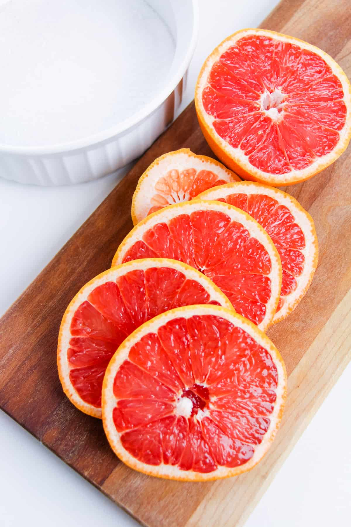 Sliced red grapefruit on wood cutting board with bowl of coarse salt next to it