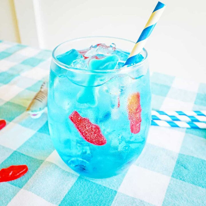 Blue ocean water drink in glass with ice, gummy fish, gummy shark, and blue and white paper straw