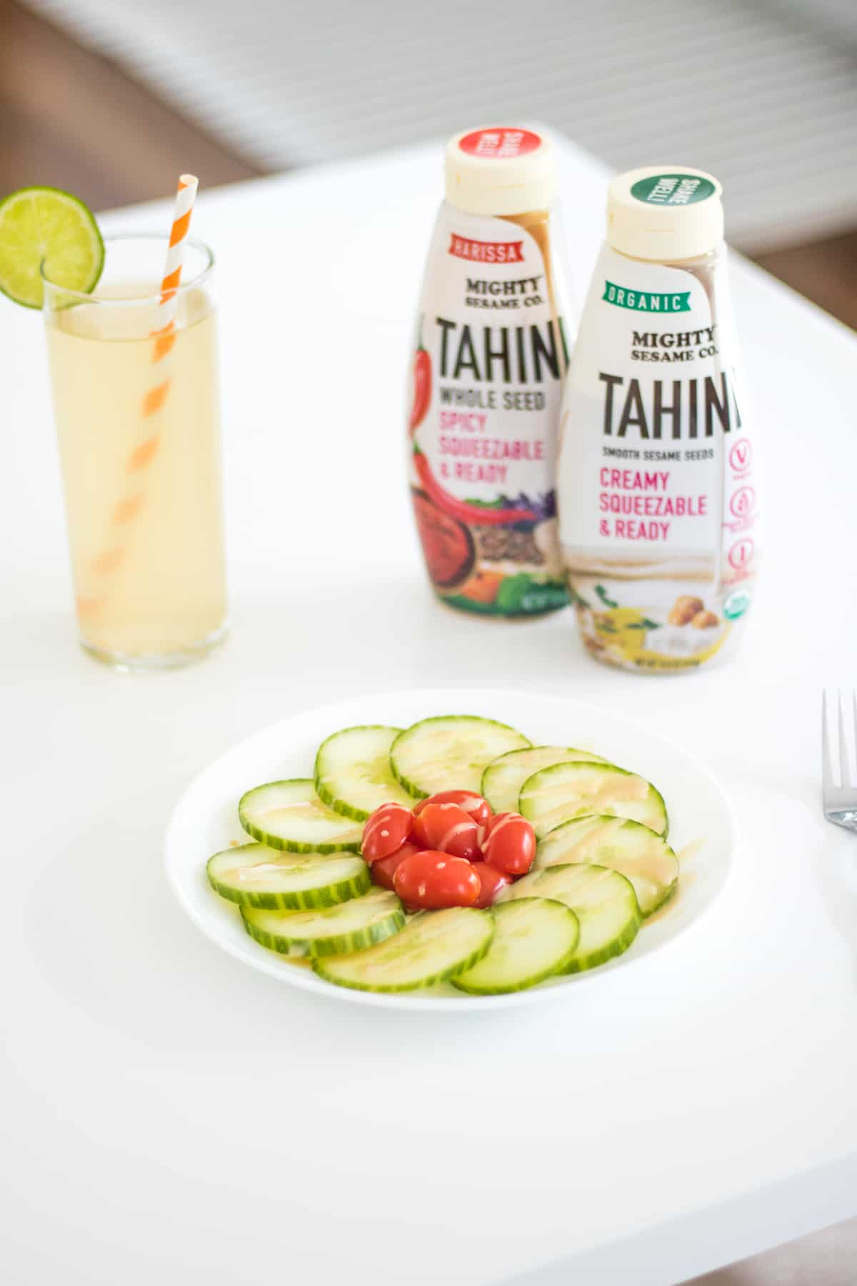 Tomato cucumbers salad with 2 bottles of squeezable tahini and a glass of sparkling water in the background